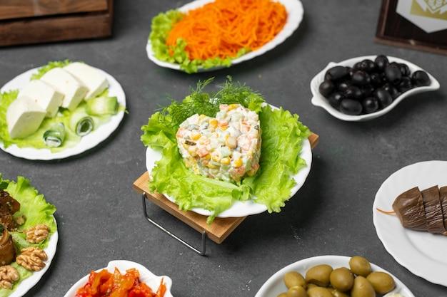 Vielzahl von marinierten nahrungsmitteln auf dem tisch mit russischem salat stolichni.