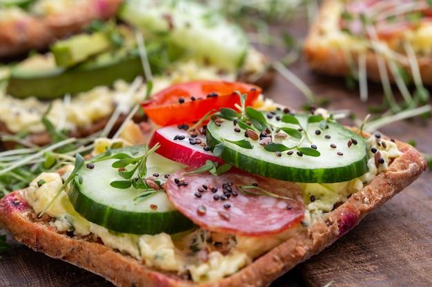 Vielzahl von mini-sandwiches mit frischkäse, gemüse und salami. sandwiches mit gurke, radieschen, tomaten, salami