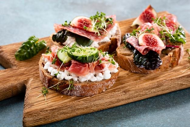 Vielzahl von mini-sandwiches mit frischkäse, gemüse und salami.