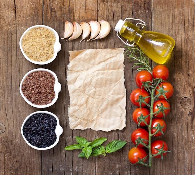 Vielzahl von reis in schalen, gemüse, kräutern und olivenöl um alten papierkopierraum auf hölzerner tischoberansicht