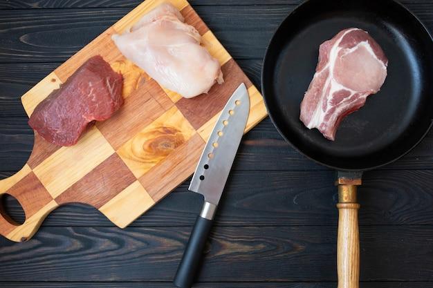 Vielzahl von rohem fleisch rindfleisch fleisch auf knochen, schweinefleisch und hühnerfilet auf holztisch mit metzgermesser, draufsicht