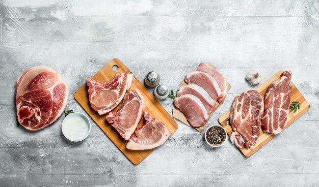 Vielzahl von rohem fleisch schweinefleisch auf einem rustikalen tisch.