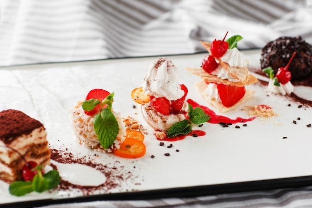 Vielzahl von süßen desserts mit tee und löffel