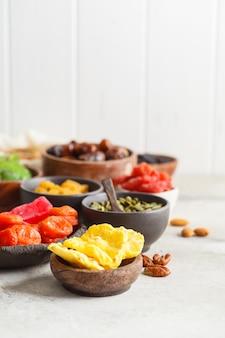 Vielzahl von trockenen früchten und von nüssen in den schüsseln, kopienraum. gesundes lebensmittelkonzept, weißer hintergrund.