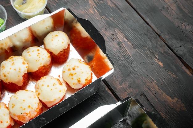 Vielzahl von verschiedenen sushi und brötchen her, lachs und thunfisch im liefernahrungskonzept, auf altem dunklem holztisch