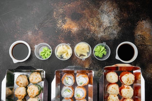 Vielzahl von verschiedenen sushi und brötchen her, lachs und thunfisch im liefernahrungskonzept, auf altem dunklem rustikalem