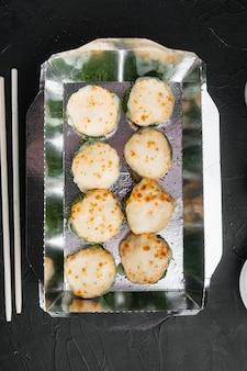 Vielzahl von verschiedenen sushi und brötchen her, lachs und thunfisch im liefernahrungskonzept, auf schwarzem stein