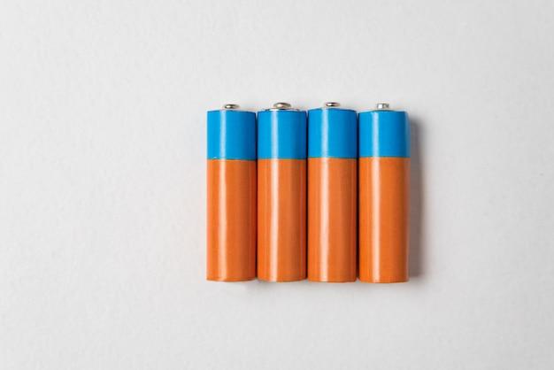 Vier aa-alkalibatterien auf weißem hintergrund. hauptbatterie für persönliche netzteile.