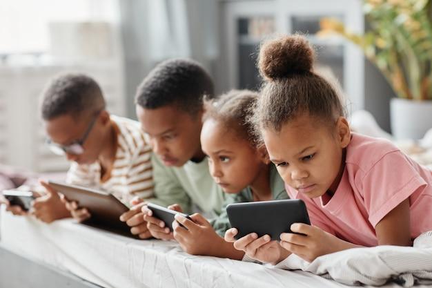 Vier afroamerikanische kinder, die hintereinander geräte verwenden, während sie zusammen auf dem bett liegen, konzept mit mehreren geschwistern