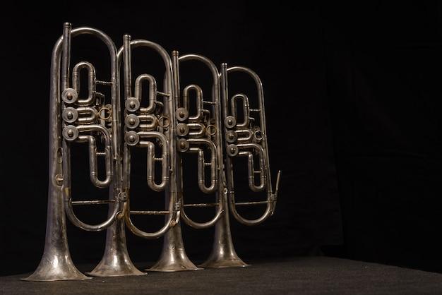 Vier alte messingblasinstrumente stehen auf einem tisch auf einem schwarzen hintergrund