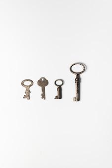 Vier alte schlüssel auf weißem hintergrund