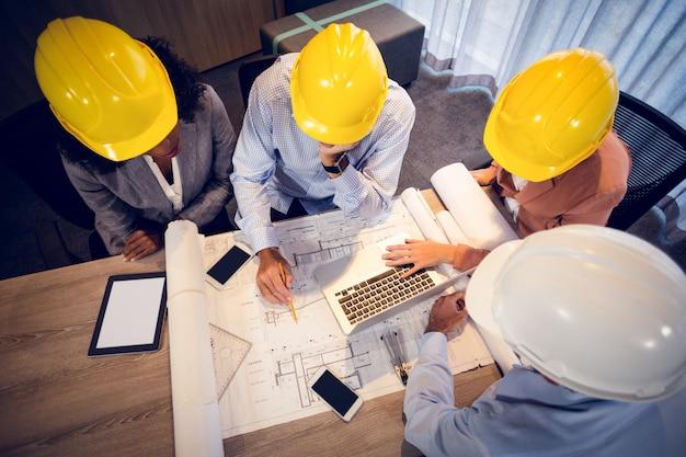 Vier architekten diskutieren in einem meeting über blaupausen