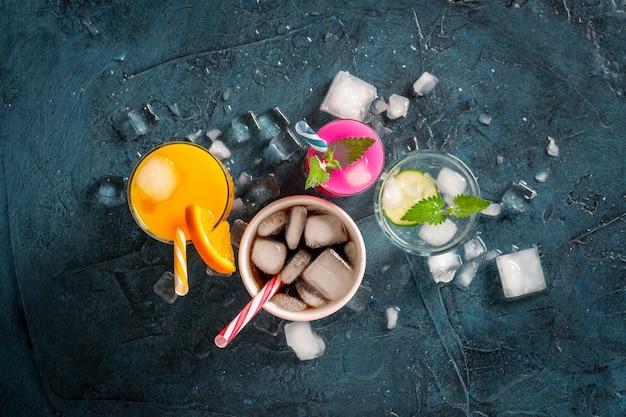 Vier arten von erfrischenden getränken mit eis auf dunkelblauem hintergrund und eiswürfeln. konzept nachtclub, nachtleben, party, durst. orange, minze und gurke, erdbeere, cola. flache lage, draufsicht