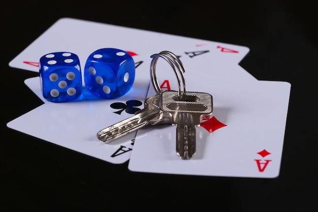 Vier asse mit würfeln und hausschlüsseln auf schwarzer oberfläche. alles steht auf dem spiel. glücksspiel