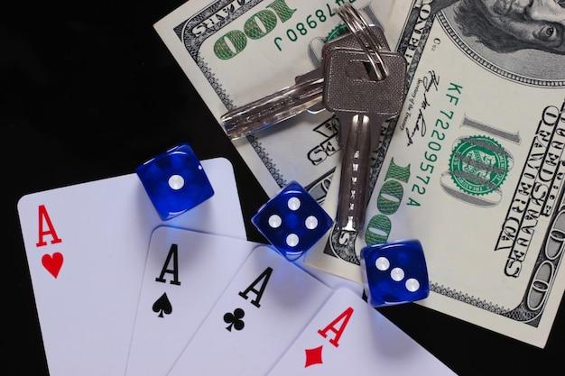 Vier asse mit würfeln und hundert dollarnoten mit hausschlüsseln auf einer schwarzen oberfläche. alles steht auf dem spiel. glücksspiel
