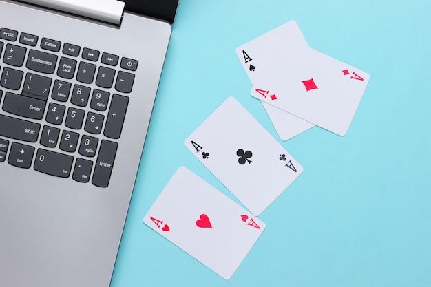 Vier asse und laptoptastatur auf blauer oberfläche. online poker casino. spielsucht
