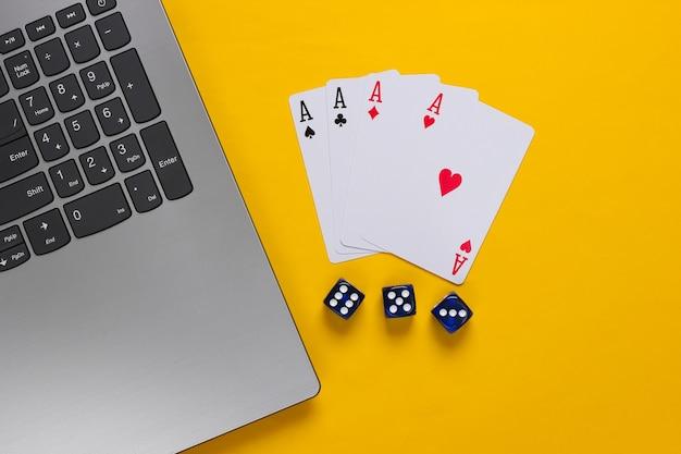 Vier asse, würfel und laptop-tastatur auf gelbem hintergrund. online poker casino. spielsucht. draufsicht