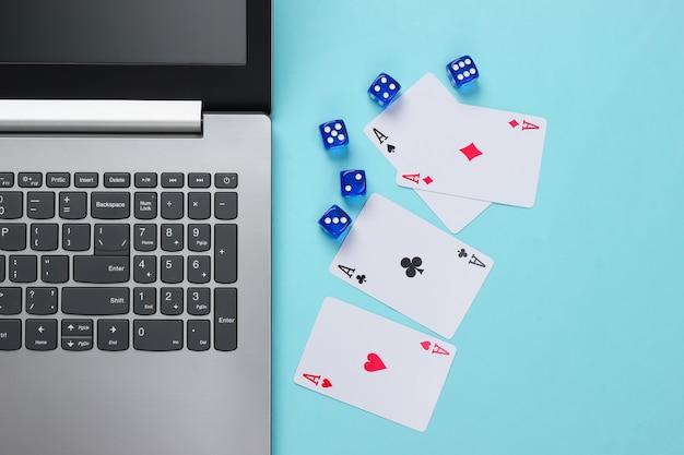 Vier asse, würfel und laptoptastatur auf blauer oberfläche. online poker casino. spielsucht