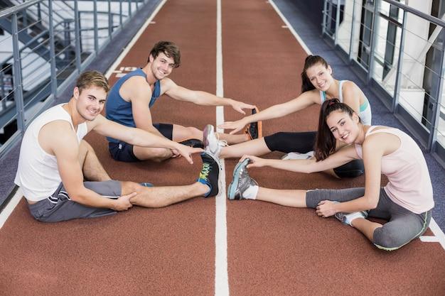 Vier athletische frauen und männer, die auf laufbahn ausdehnen