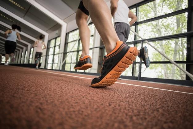 Vier athletische frauen und männer, die auf laufbahn laufen