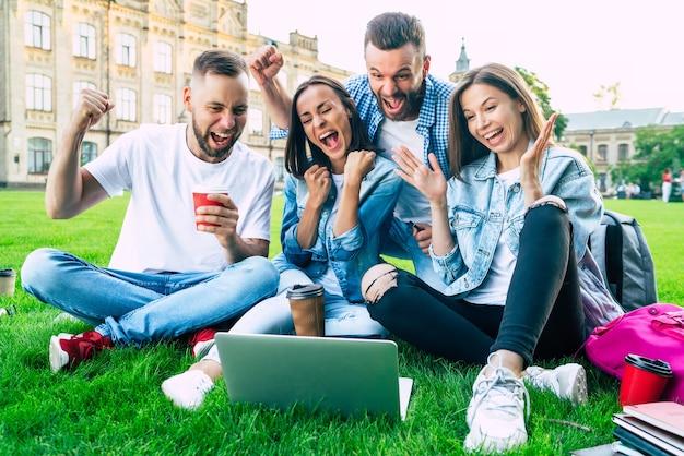 Vier beste junge studentenfreunde mit einem laptop auf dem rasen im universitätsgebiet sind glücklich und aufgeregt