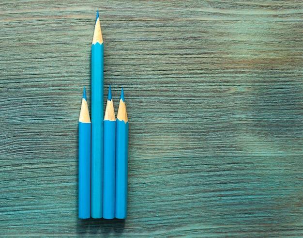 Vier blaue bleistifte unterschiedlicher länge, ein langer, drei kurze auf türkisfarbenem naturholztisch in nahaufnahme. draufsicht. selektiver weichzeichner. . textkopierplatz.
