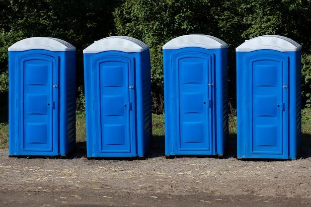 Vier blaue tragbare toilettenstände aus kunststoff im park