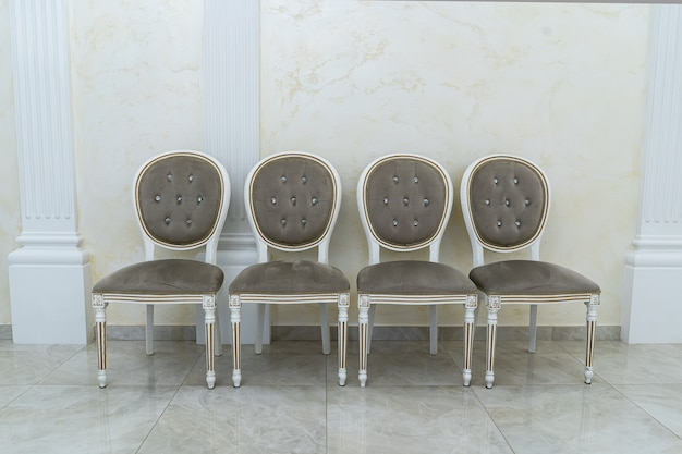 Vier braune antike stühle stehen in einer reihe.