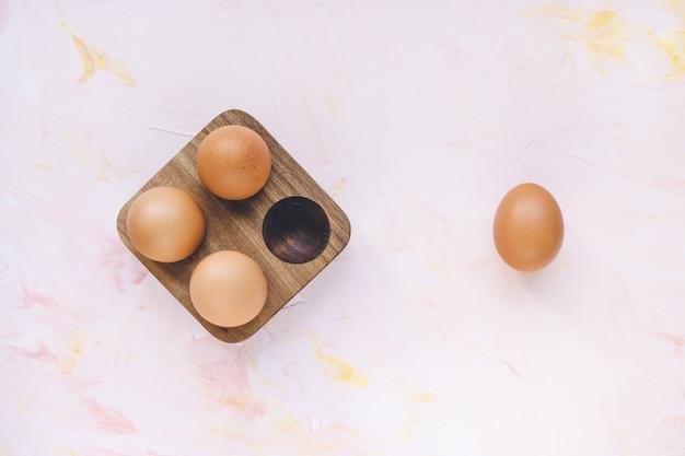 Vier braune eier in einem hölzernen speicherorganisator bo