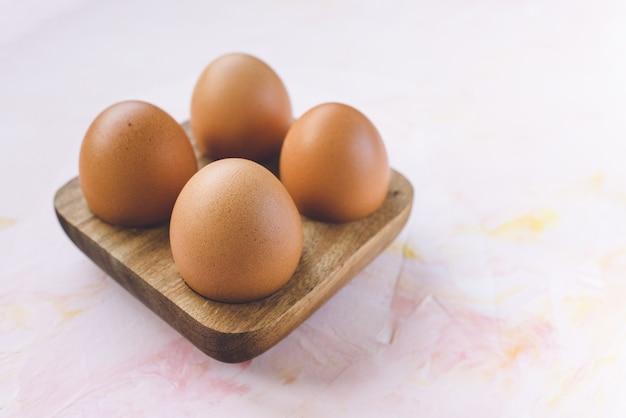 Vier braune eier in einer hölzernen aufbewahrungsbox