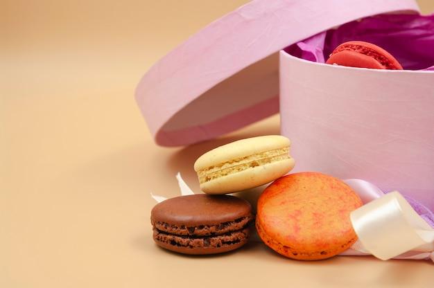 Vier bunte französische macarons mit rosa pappkarton auf pfirsichhintergrund freier speicherplatz