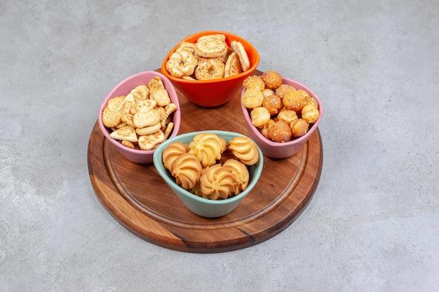 Vier bunte schalen mit knusprigen keksen und kekschips auf holzbrett auf marmorhintergrund. hochwertiges foto
