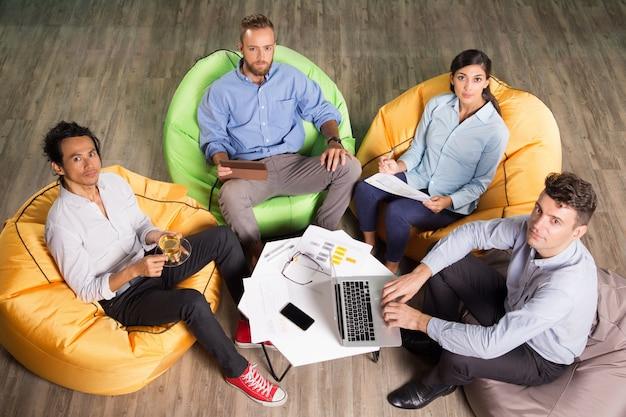 Vier business-leute sitzen auf sitzsack stühle