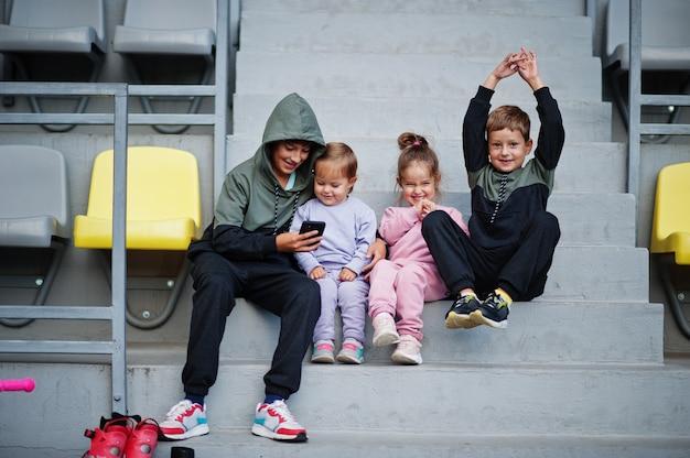 Vier cuttie-kinder sitzen auf dem sportplatz und schauen auf das handy.