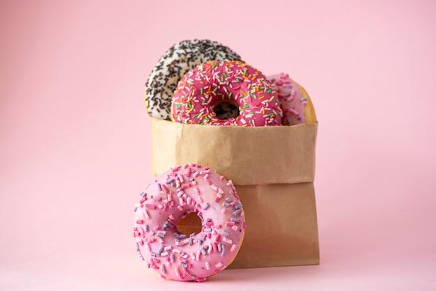 Vier donuts mit glasur in einer papiertüte