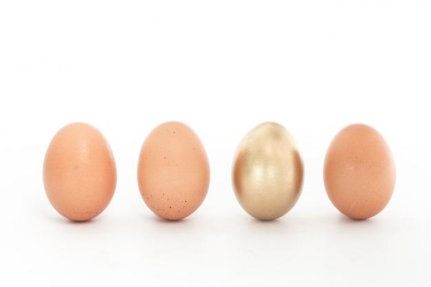 Vier eier in einer reihe mit einem gold eins