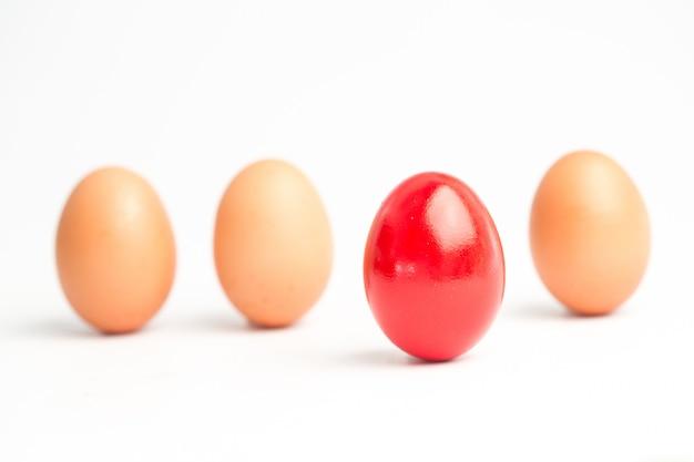 Vier eier in folge mit einem roten herausstehen
