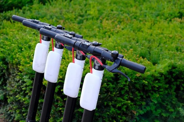 Vier elektroroller parkten in einer reihe auf dem bürgersteig der stadt.