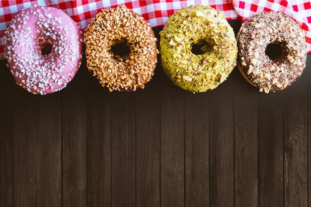 Vier fantastische amerikanische donuts auf einem holztisch