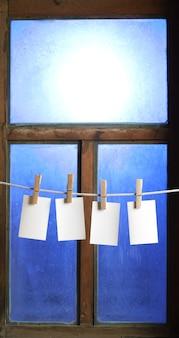 Vier fotopapiere mit wäscheklammern am fensterhintergrund am seil befestigen