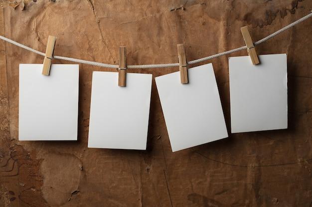 Vier fotopapiere mit wäscheklammern auf papierhintergrund am seil befestigen