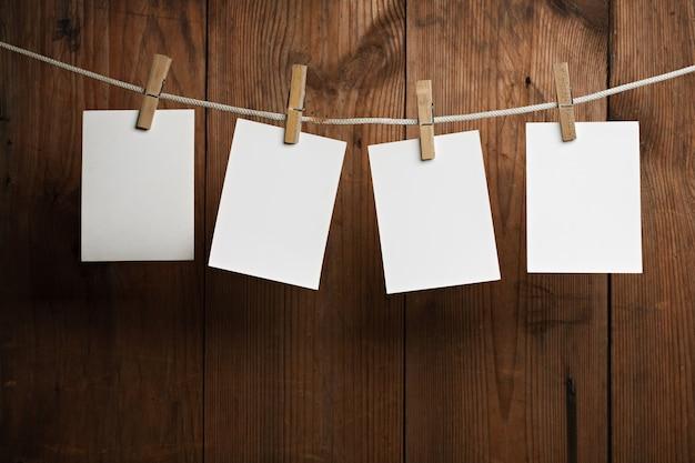 Vier fotopapiere werden mit wäscheklammern auf holzuntergrund am seil befestigt