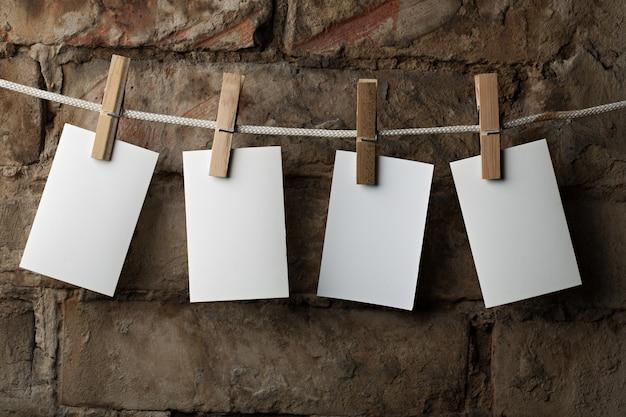 Vier fotopapiere werden mit wäscheklammern auf ziegelhintergrund am seil befestigt