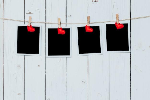 Vier fotorahmen leer und rotes herz hängen auf weißem holz hintergrund mit platz