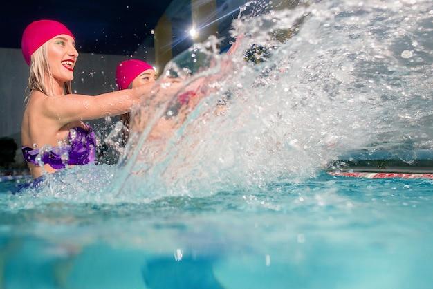 Vier frauen in bunten badeanzügen und rosa bademützen im schwimmbad