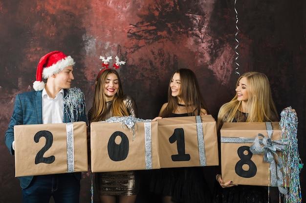 Vier freunde, die 2018 mit kästen feiern