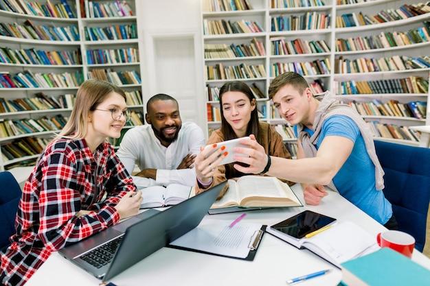 Vier freunde, gut aussehende fröhliche glückliche studenten gemischter rassen, die smartphone auf lustigem video betrachten