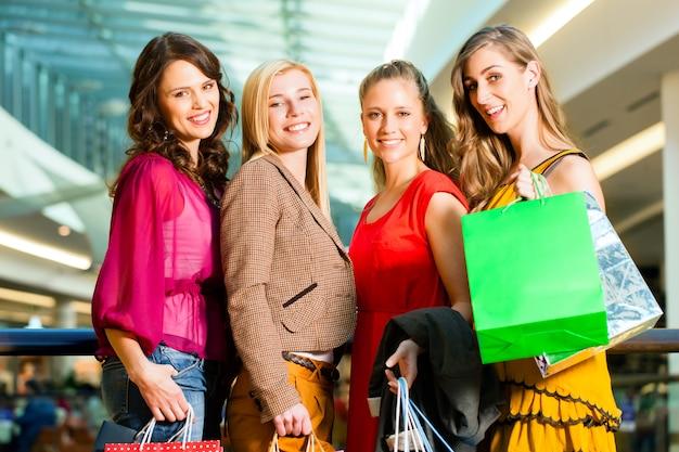 Vier freundinnen, die in einem mall kaufen
