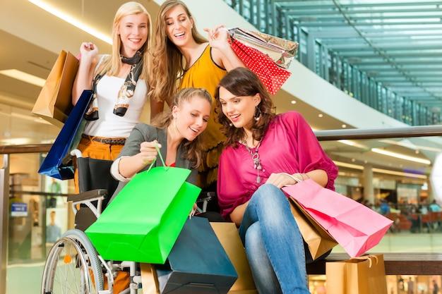 Vier freundinnen, die in einem mall mit rollstuhl kaufen