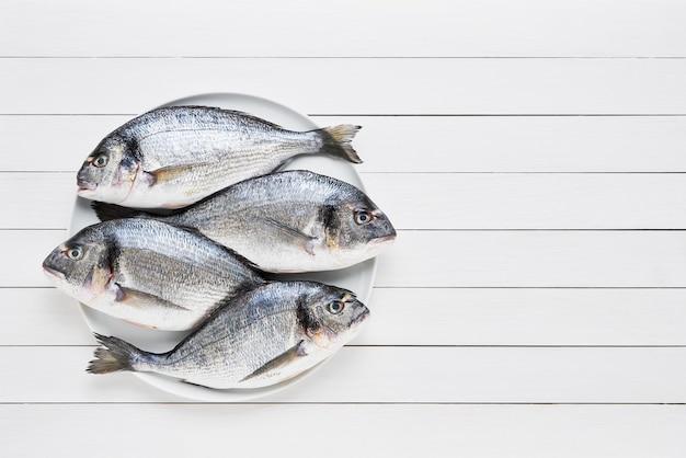 Vier frische brassenfische mit vergoldetem kopf auf einer schüssel auf einem weißen holztisch. gesundes lebensmittelkonzept. draufsicht